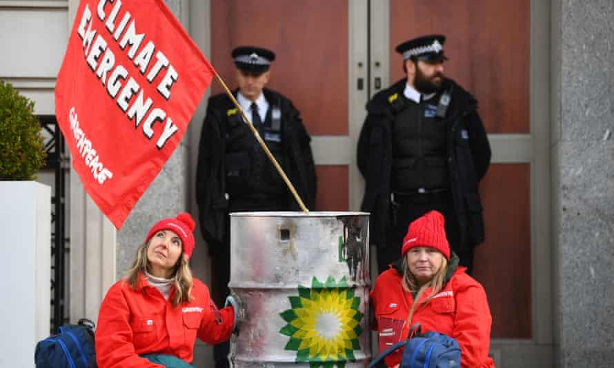 Police officers stand near activists locked to dirty oil barrels who blocked BP's headquarters in London to mark the first day of the oil giant's new chief executive.