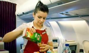 A female cabin crew member serves drinks on a Virgin Atlantic flight