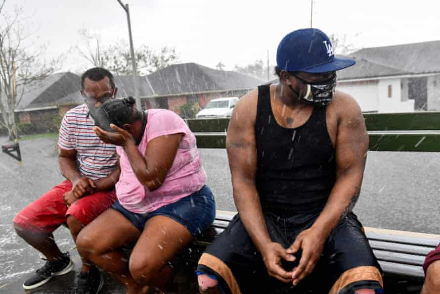 Darrin Heisser, right, reacts to a sudden rain shower as people evacuate from a flooded neighborhood in LaPlace, Louisiana, near New Orleans.
