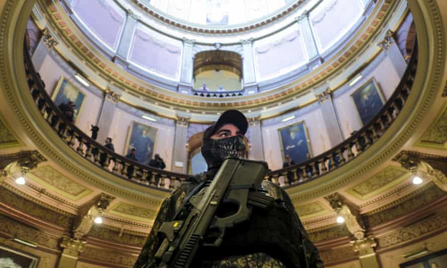 An armed protester stands at the Michigan capitol building in Lansing, Michigan, on 30 April.