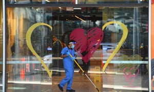 A person cleans the entrance of the Novotel Melbourne South Wharf hotel on Wednesday. Floor managers employed by contractor Spotless have been stood down and replaced by Victoria police after people working at the hotel contracted Covid-19.