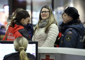 A woman reacts next to Russian Emergencies Ministry members at Pulkovo airport in St. Petersburg