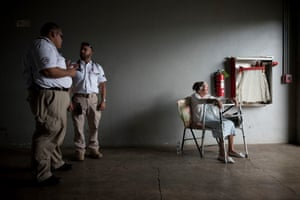 Palmita Cruz, 84, looks on as two paramedics talk inside a shelter in Guanica