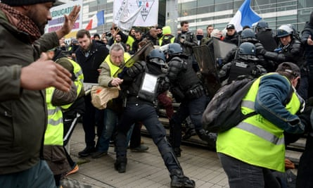 Yellow vest protesters are forced back by riot police in Paris