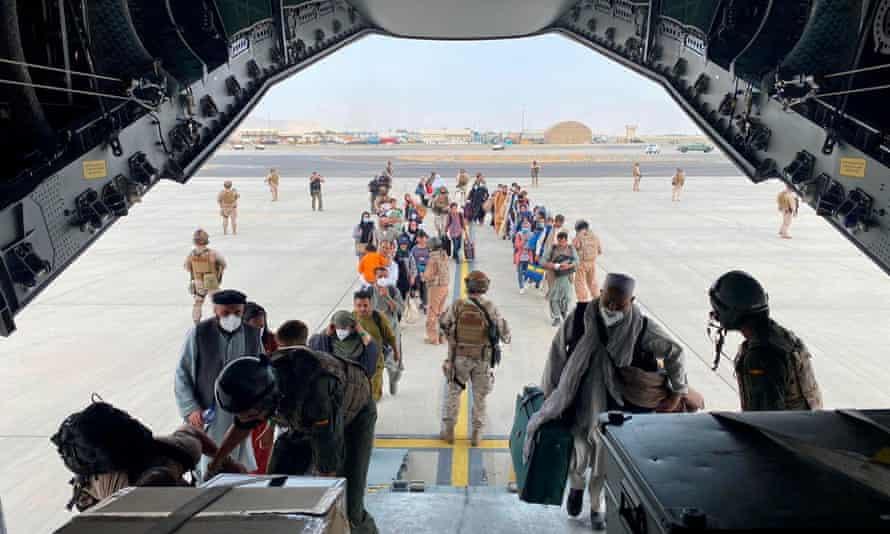Afghans board a military plane at the Hamid Karzai International Airport, Kabul.