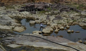 An Indian villager walks between rocks as he crosses a depleted reservoir in Tikamgarh in the central Indian state of Madhya Pradesh.