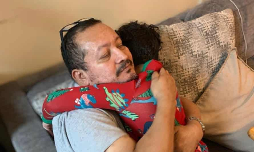 Asmel Matamoros hugging one of his grandchildren.