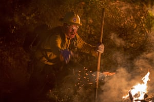 A firefighter fights flames in chaparral brush using only a hand tool at the La Tuna Fire on September 2, 2017 near Burbank, California