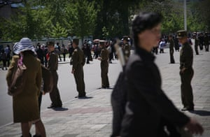 Pyongyang, North Korea North Korean soldiers stand by a sidewalk while people carrying decorative flowers make their way from the Kim Il Sung Square