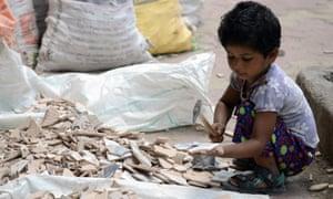 An Indian child breaks apart broken tiles outside an under-construction apartment building in Mumbai.
