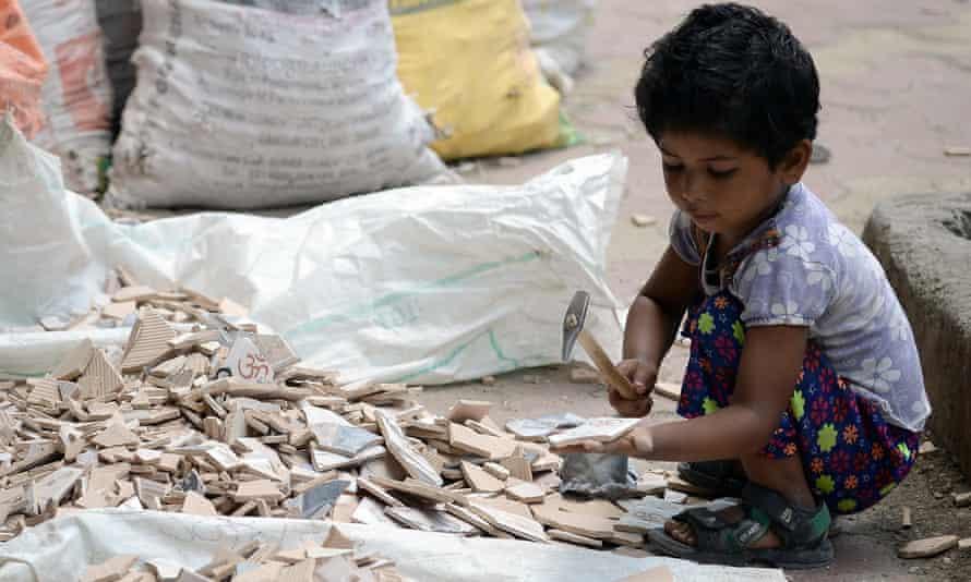 An Indian child breaks apart broken tiles