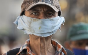 A man uses a makeshift face mask made of a piece of cloth at a street market in Caracas, Venezuela