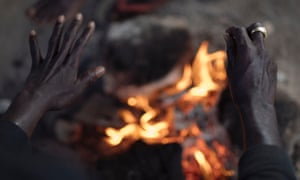 A worker warms his hands over a fire as night falls at the migrant camp in Campobello di Mazara.