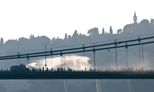 A police armoured vehicle uses a water cannon to disperse protesters on the Bosphorus bridge