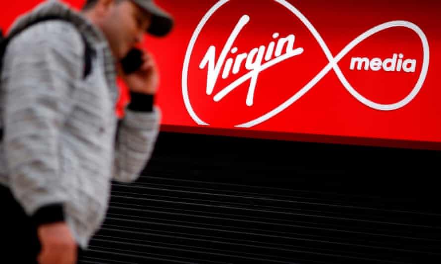 a man passes a VirginMedia sign