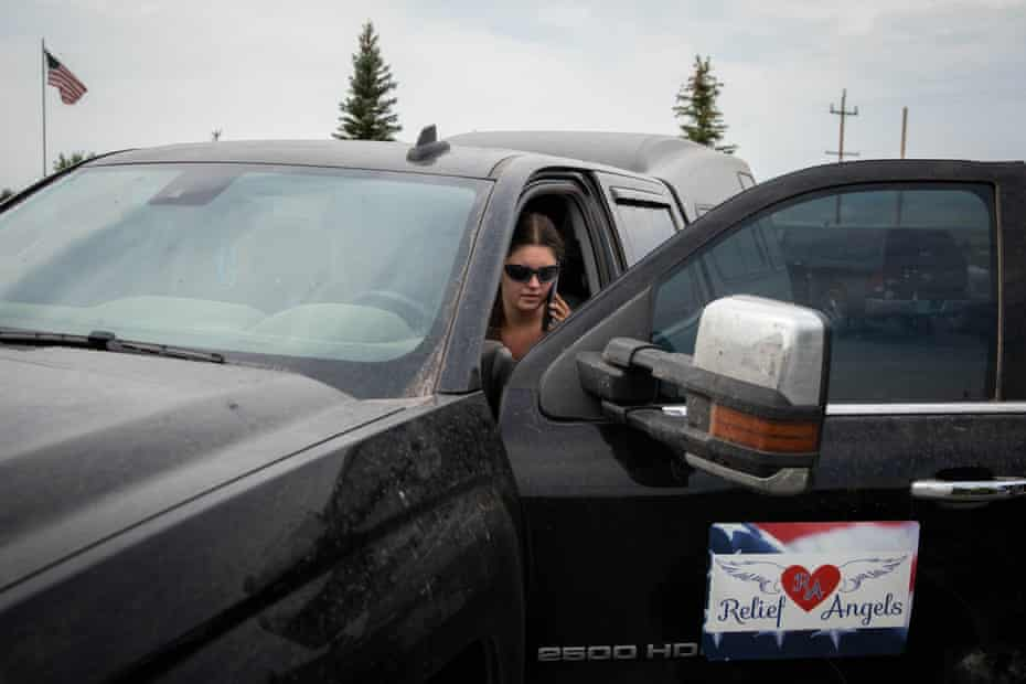"""Valerie O'Dai speaks to a donor in her truck that has """"Relief Angels"""" on the door."""
