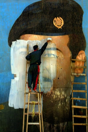 An image of Saddam Hussein, riddled with bullet holes, is painted over by Salem Yuel at what was once a Fedayeen guerrilla training camp in Baghdad