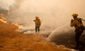 Firefighters work a hotspot caused by the Woosley fire in Malibu, California, on Saturday.