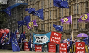 A mix of remain and leave supporters wave flags waving flags outside the Houses of Parliament.