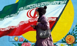 An Iranian woman walks in front of a painting of the national flag in a street of Tehran on Wednesday. Iran could see US sanctions start to be lifted as early as January.