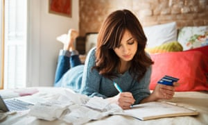 woman planning purchases on bed