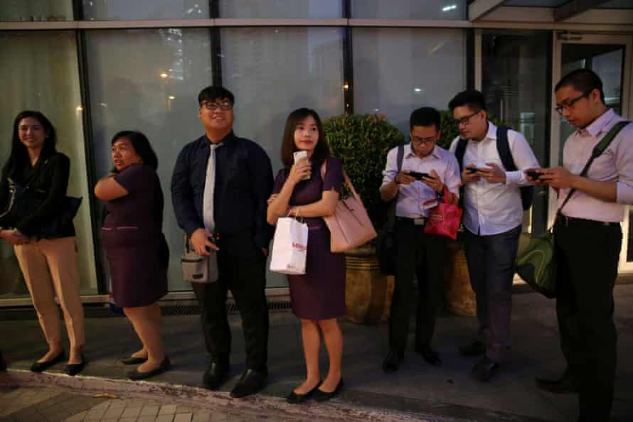 Janice Sarad, 22, who works for a bank, queues for her company's free shuttle service going to the train station, in Taguig City