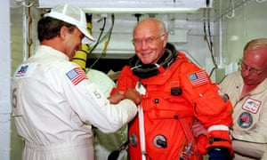 John Glenn getting a hand from white room technicians moments before boarding the US space shuttle Discovery.