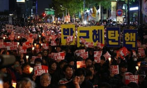 People holding placards reading 'Park Geun-Hye out' march in Seoul