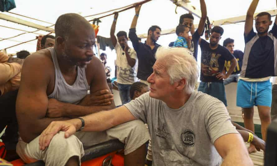Richard Gere talking to migrants onboard the Proactiva Open Arms ship.