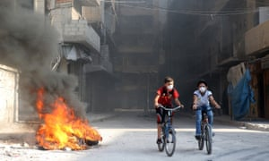 Syrian children cycle past tyres in Aleppo.