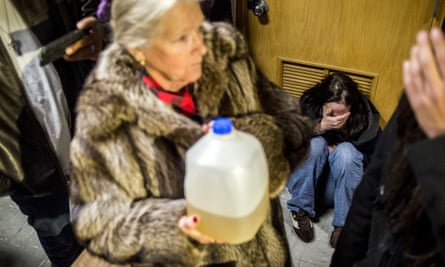 Flint resident Andrew Watson drops to the floor in tears and a resident holds a jug of contaminated water as Flint police stand guard at the city council chamber doors.