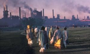 Indian women walk towards a coal plant at sunrise.