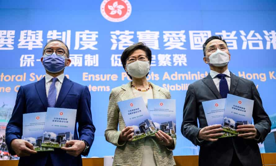 Carrie Lam (centre) held a press conference on the new measures in front of a backdrop that read: 'Improve Electoral System, Ensure Patriots Administering Hong Kong.'
