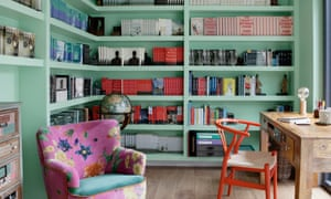 Pale blue shelving along two walls of a room with John Boyne's books neatly arranged; a pink and blue comfy chair and a small, simple wooden desk and chair