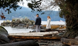 A couple walks on the beach outside the property in North Saanich, British Columbia, where according to news reports Prince Harry and Meghan spent the holidays at the end of 2019.