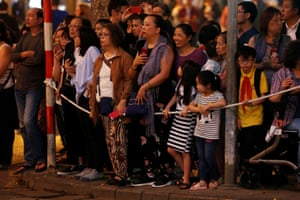 Bystanders wait to see the motorcade of Donald Trump in Hanoi