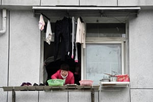 A woman places food to dry outside on a laundry rack in Wuhan