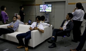 Japanese journalists watch a TV broadcast displaying US president Barack Obama during his visit to the Hiroshima Peace Memorial Park