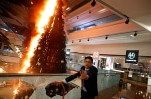 A man reacts as he tries to extinguish a burning Christmas tree at the Festival Walk mall in Kowloon Tong, Hong Kong.