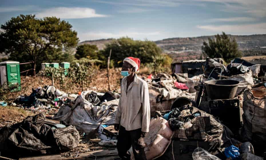 A resident of Plot 323 in Wilgespruit, Johannesburg, stands among sacks of recycled items