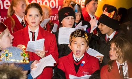 Schoolchildren sing Christmas carols.