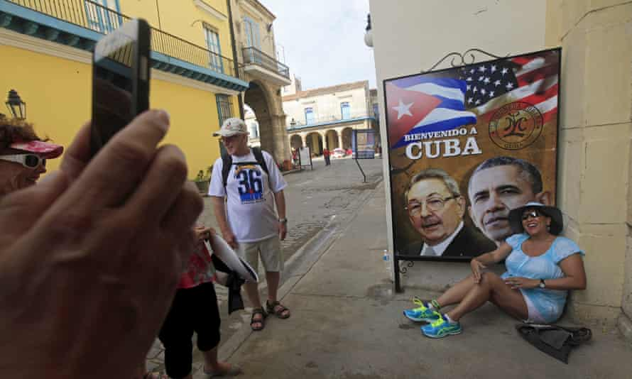 A tourist has her picture taken next to images of Raul Castro and Barack Obama in Havana, March 19, 2016.