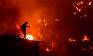 A Bangladeshi man tries to extinguish flames as a fire ravages a slum in Dhaka.