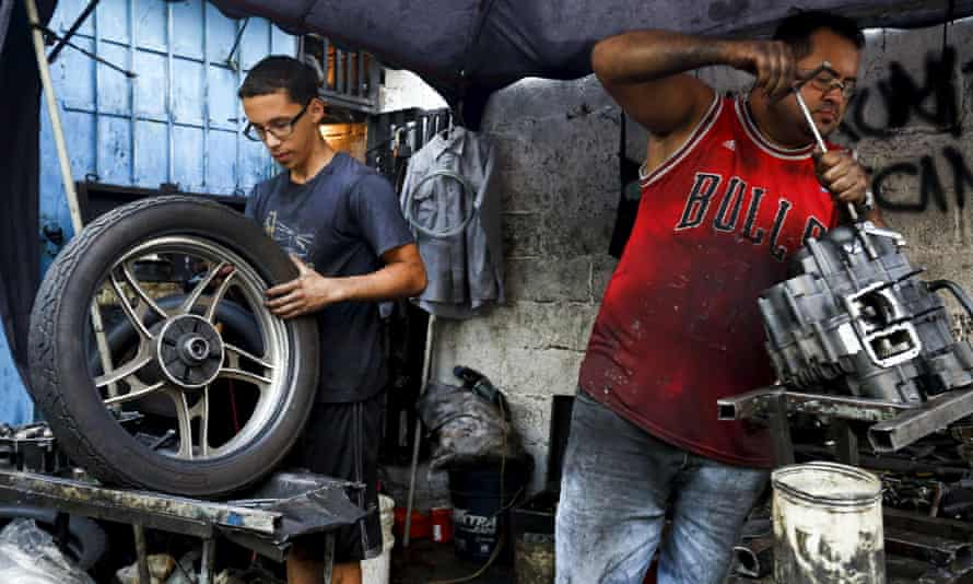 Motorcycle mechanics work at a makeshift repair shop on the street in Caracas.