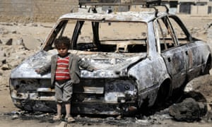 A Yemeni child next to a wrecked car after Saudi-led airstrikes in Sanaa, Yemen, in February 2016.