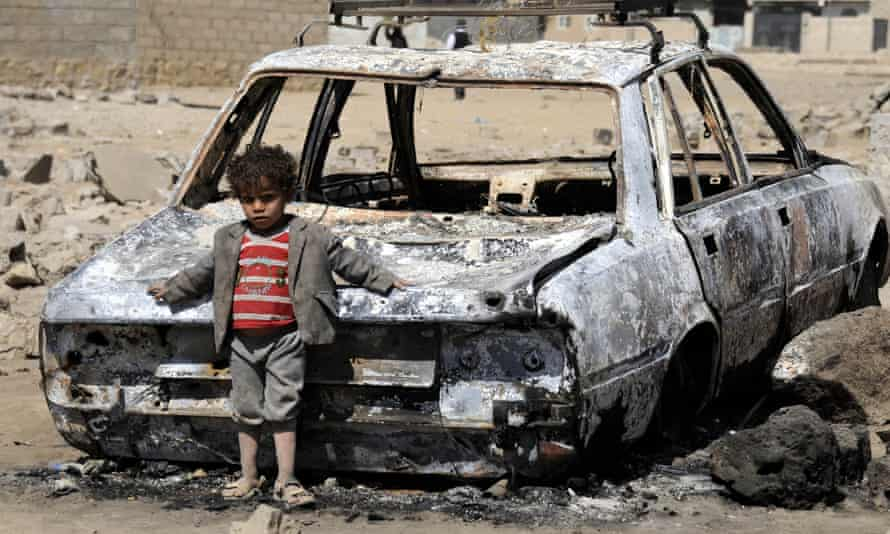 A Yemeni child leans on the wreckage of car after airstrikes by Saudi Arabia on Sana'a, Yemen.