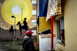 Two residents chat in front of a mural by Portuguese artist Slap