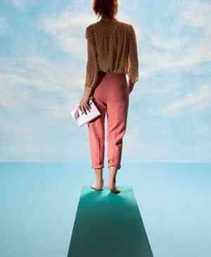 A model standing on a diving board looking at the horizon, and holding a pad and pen