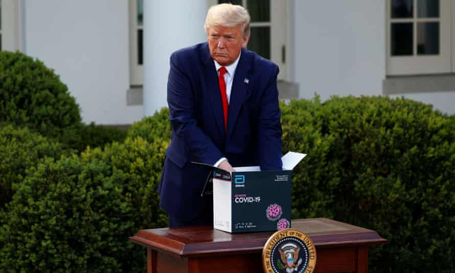 Donald Trump with a coronavirus test kit at a White House briefing, 30 March 2020