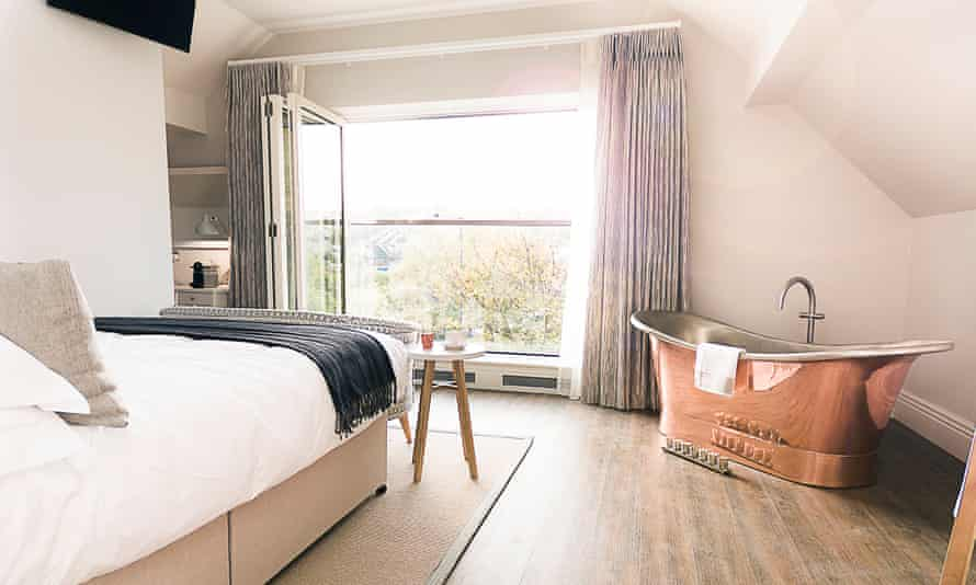 A bed facing a large window and a gold, roll-top bath at Brocco on the Park, Sheffield